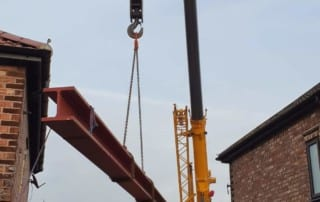 a 7 meter structural steel beam being lifted into place by a crane